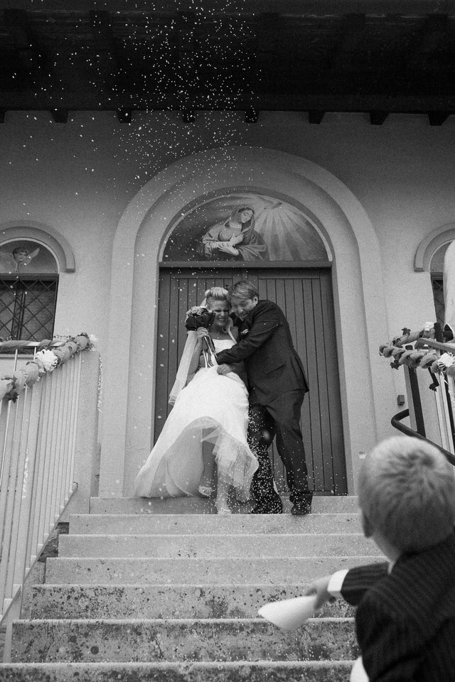 Black and white photo of newly wedded couple showered with confetti