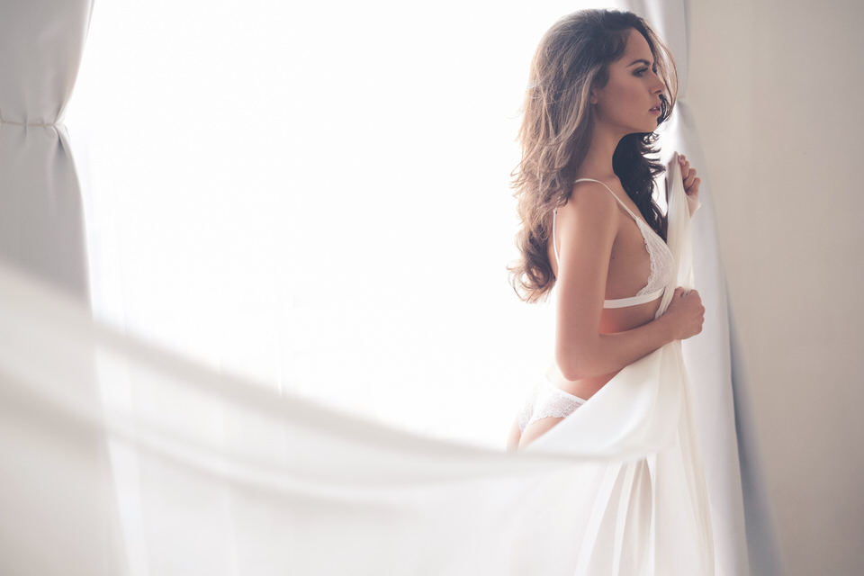 A photo of a woman in bridal lingerie holding a veil