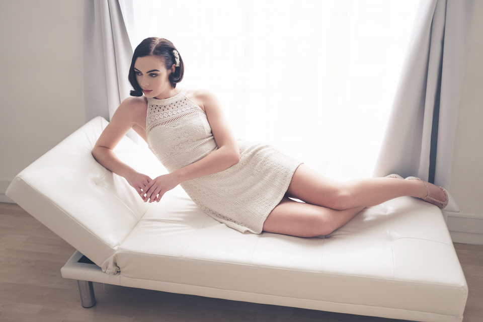A photo of a woman lying on a couch in a white dress