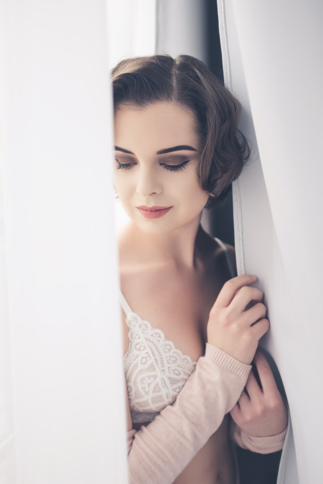 A photo of a woman standing in between some curtains in bridal lingerie