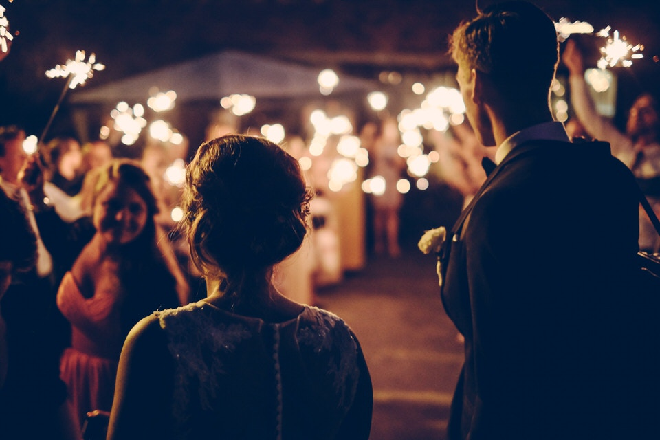 An evening wedding shot with bokeh lights and people