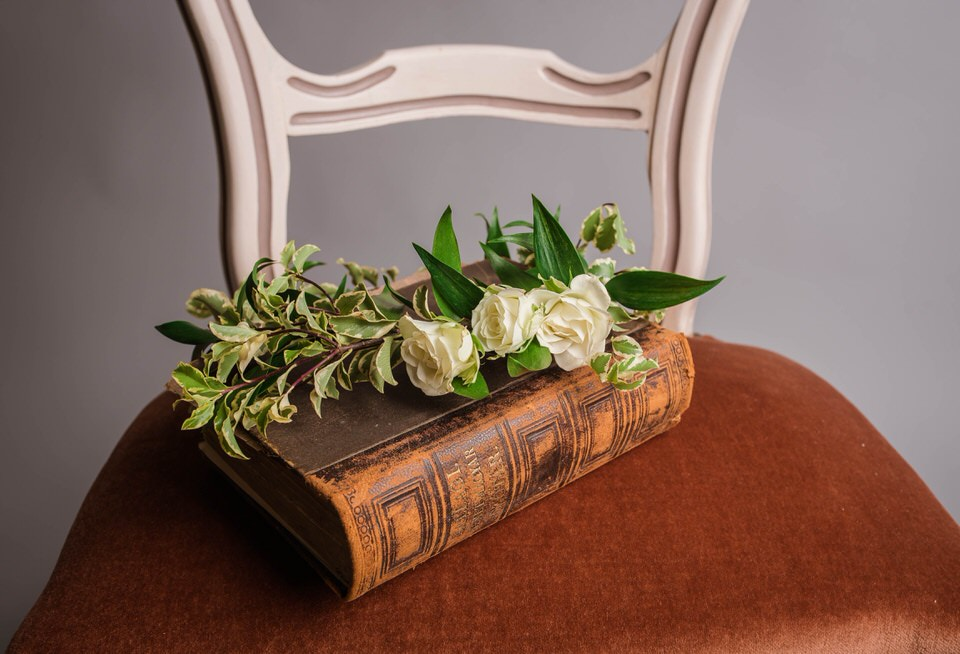 A photo of a book and a flower placed on a chair