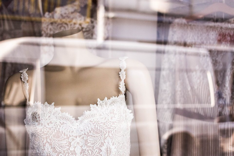 A photo of a shop window with many types of wedding dresses inside