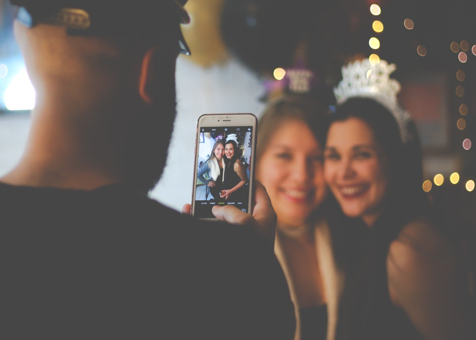 A photo of a man taking a photo of two girls on an iphone