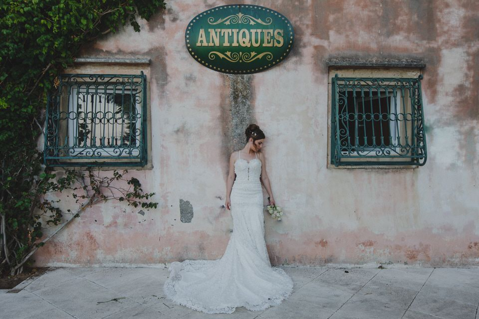 A photo of a woman in a mermaid wedding dress on the backdrop of an old villa