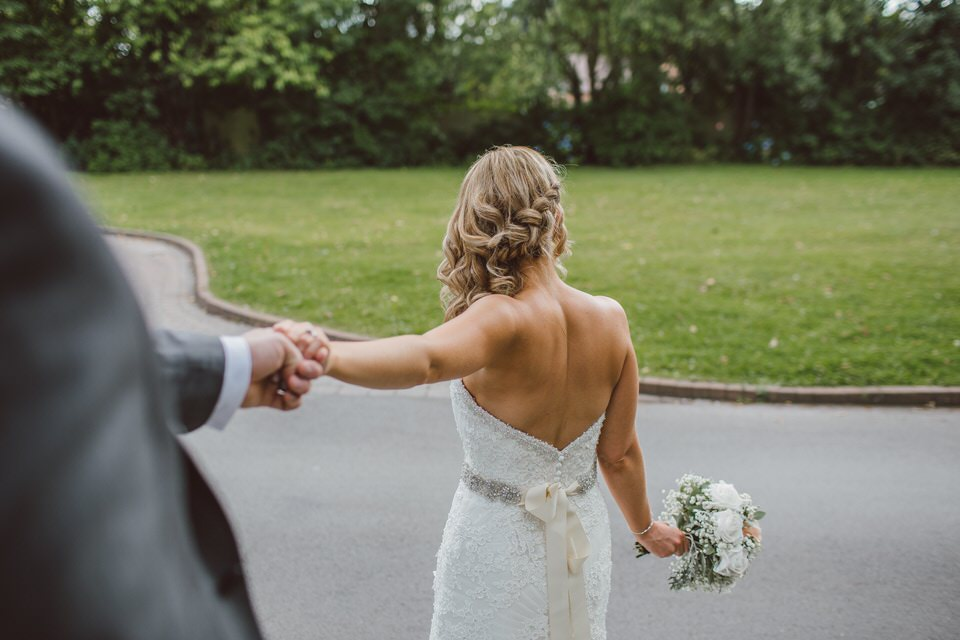 A photo of a new bride holding her husband's hand in a column shaped wedding dress